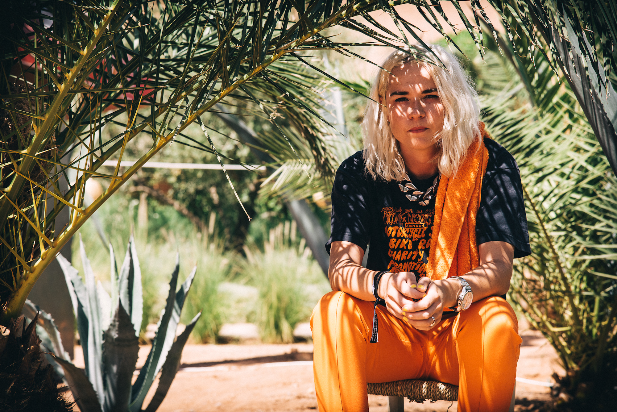 Australian DJ and producer HAAi, aka Teneil Throssell orange sitting