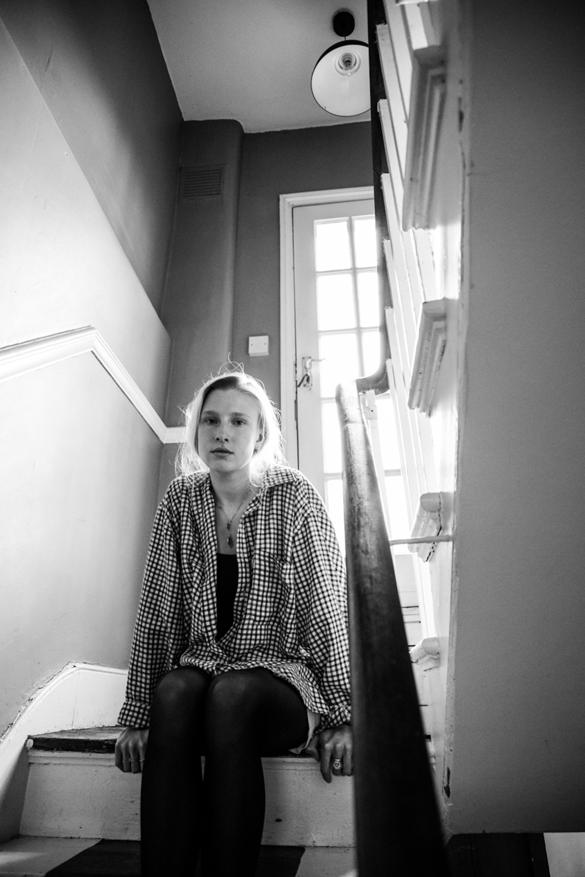 Billie Marten in London sitting on staircase black and white