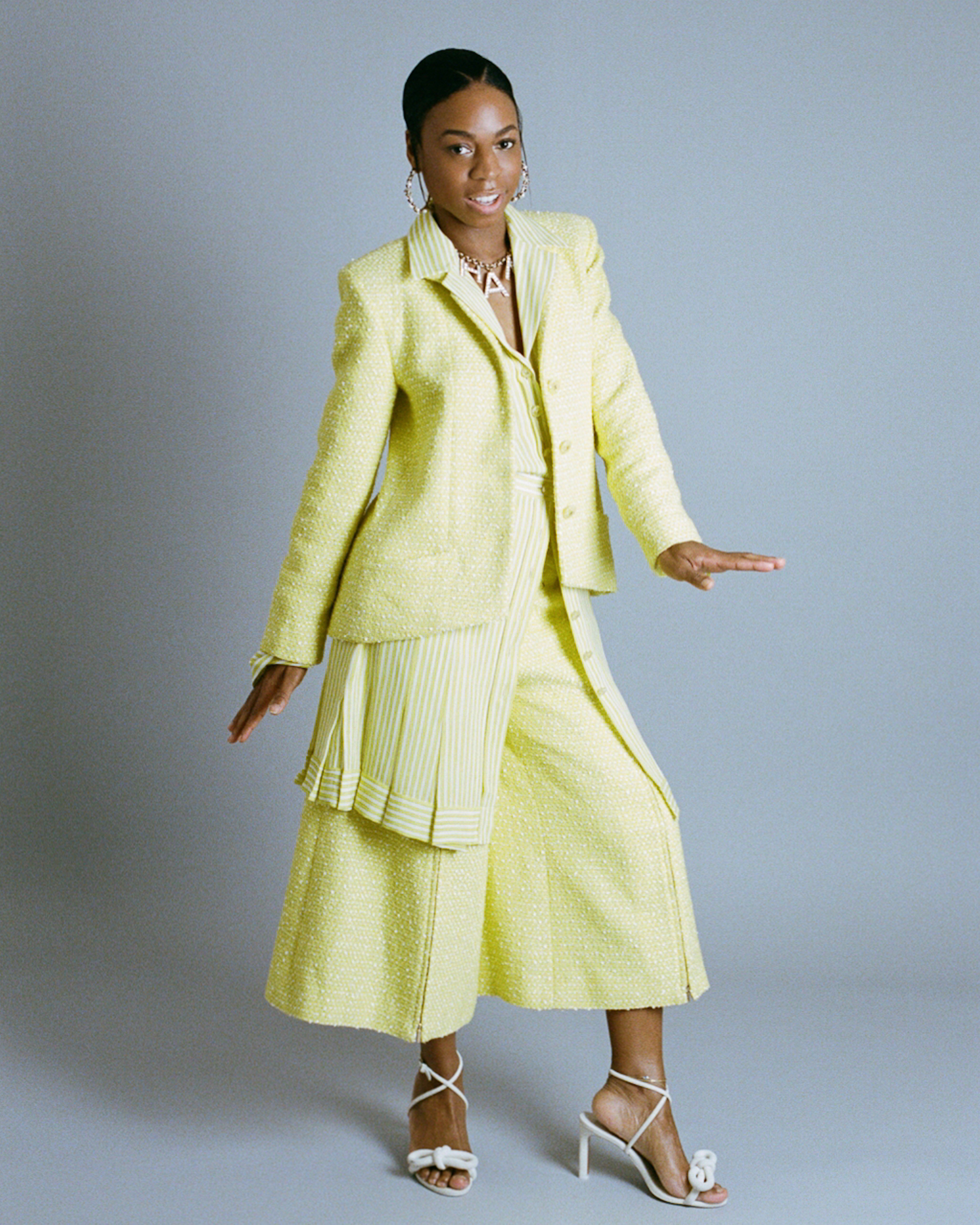 Pippa Bennett-Warner in yellow suit full-length dancing