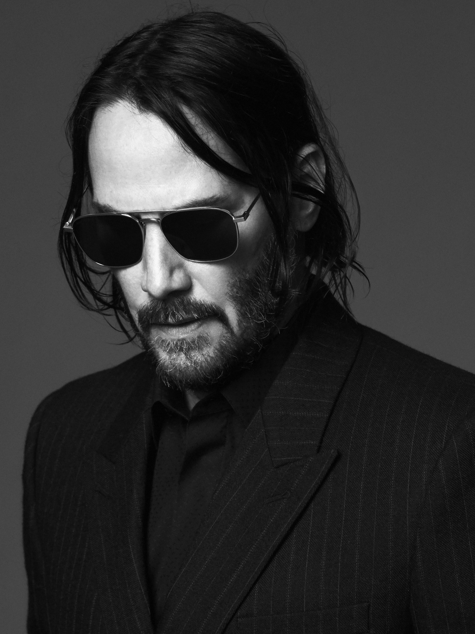 Keanu Reeves is the face of Saint Laurent Fall 2019 menswear campaign in a pinstripe suit