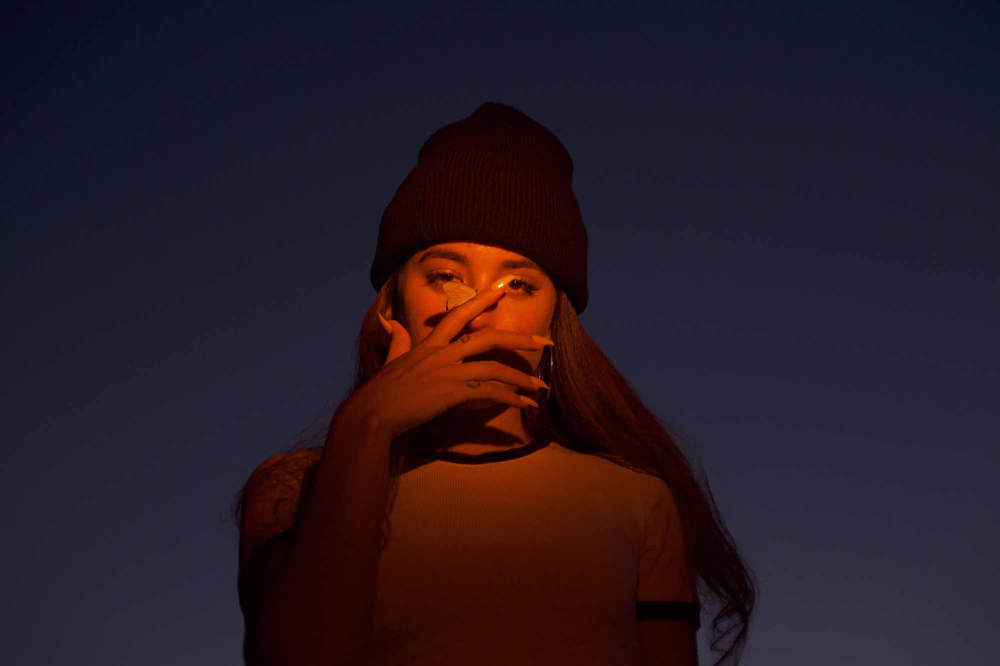 Alaina Castillo press image hat hand covering face