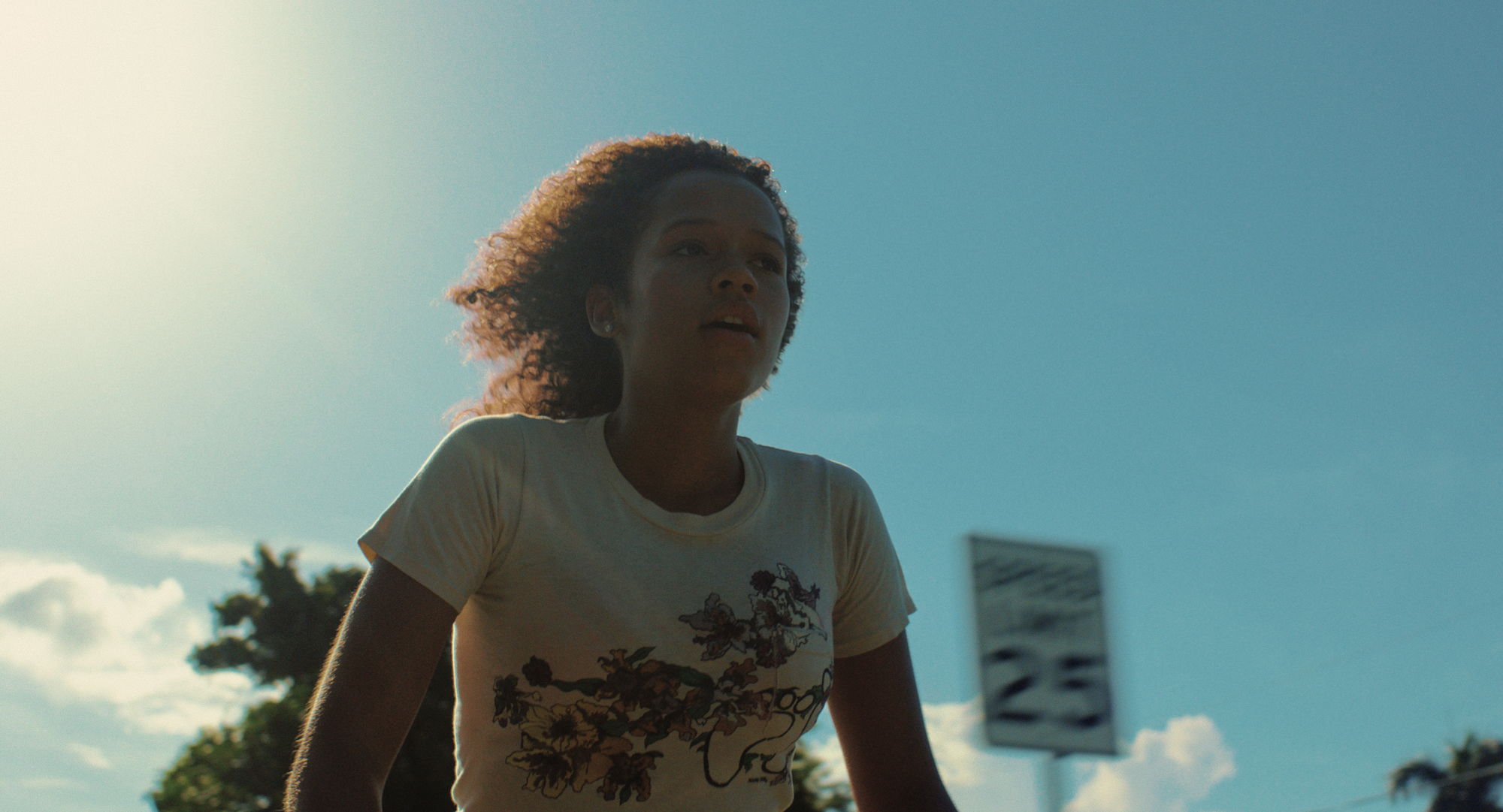 Taylor Russell in A24's Waves riding bicycle