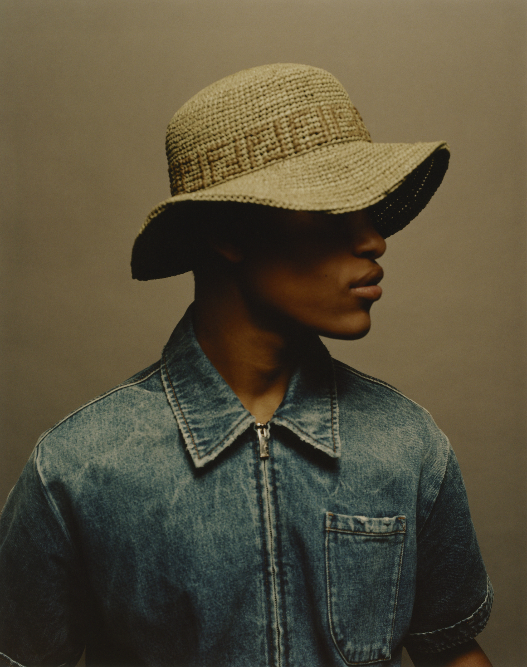 Fendi fashion editorial taken from out Spring issue model wears Fendi sunhat and denim shirt