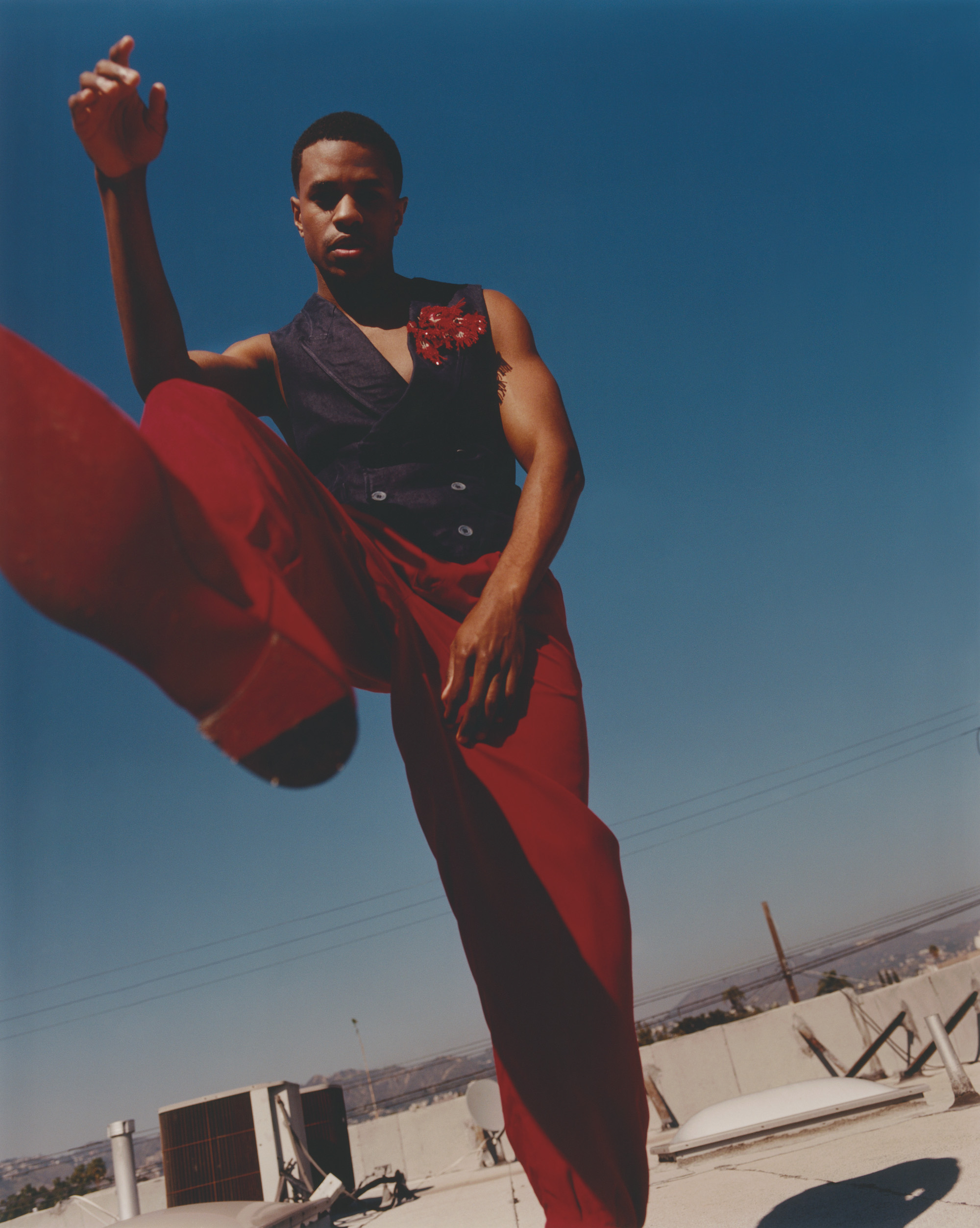 Jeremy pope for rollacoaster wearing a read waist coat and trousers