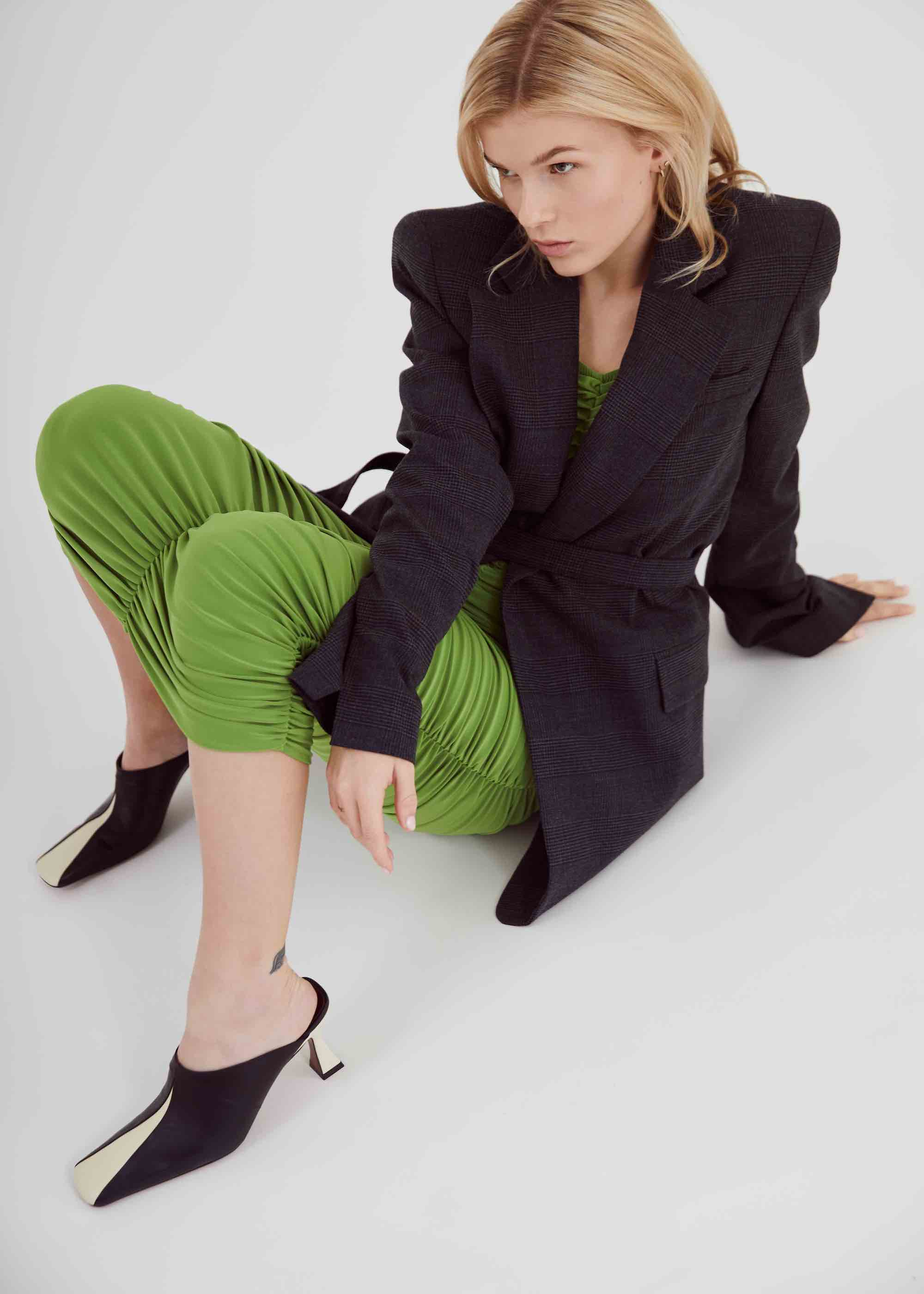 Nykki wears black blazer and green joggers