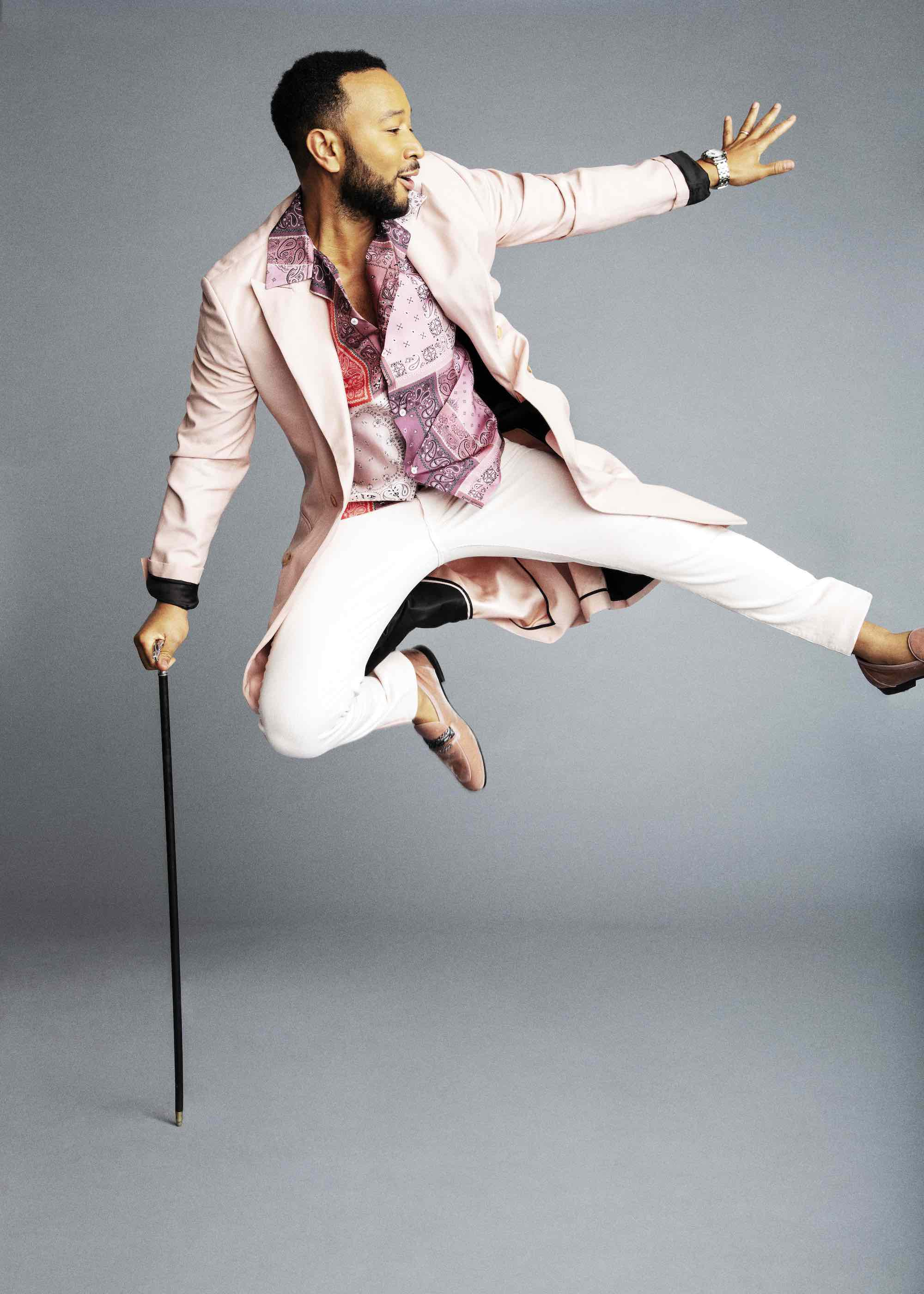 John Legend in a pink suit and cane jumping