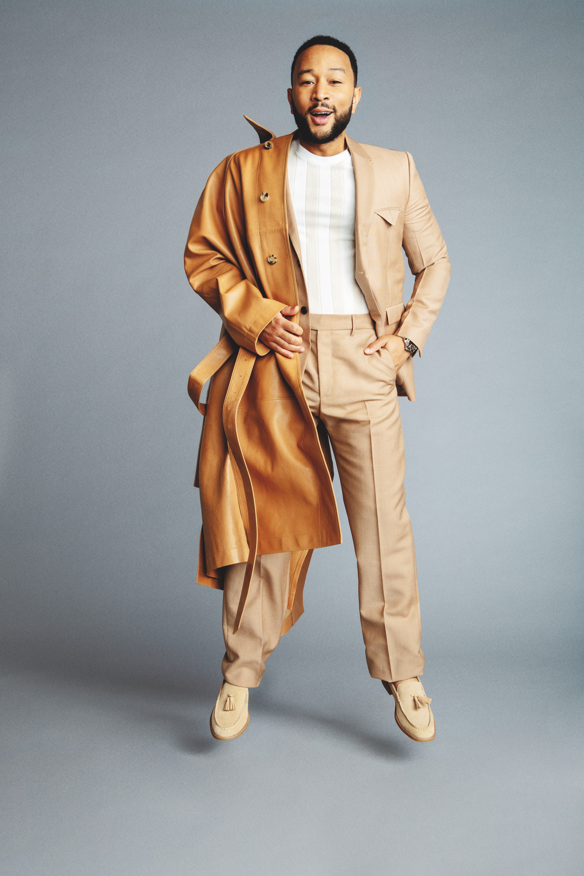 John Legend for Rollacoaster in beige coat jumping in white shirt