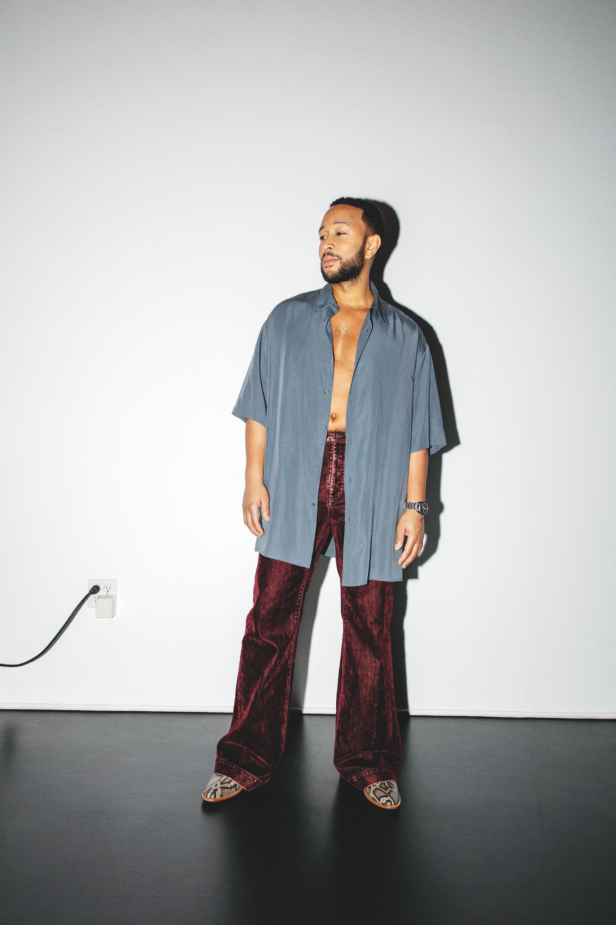 John Legend wearing open blue shirt with red trousers