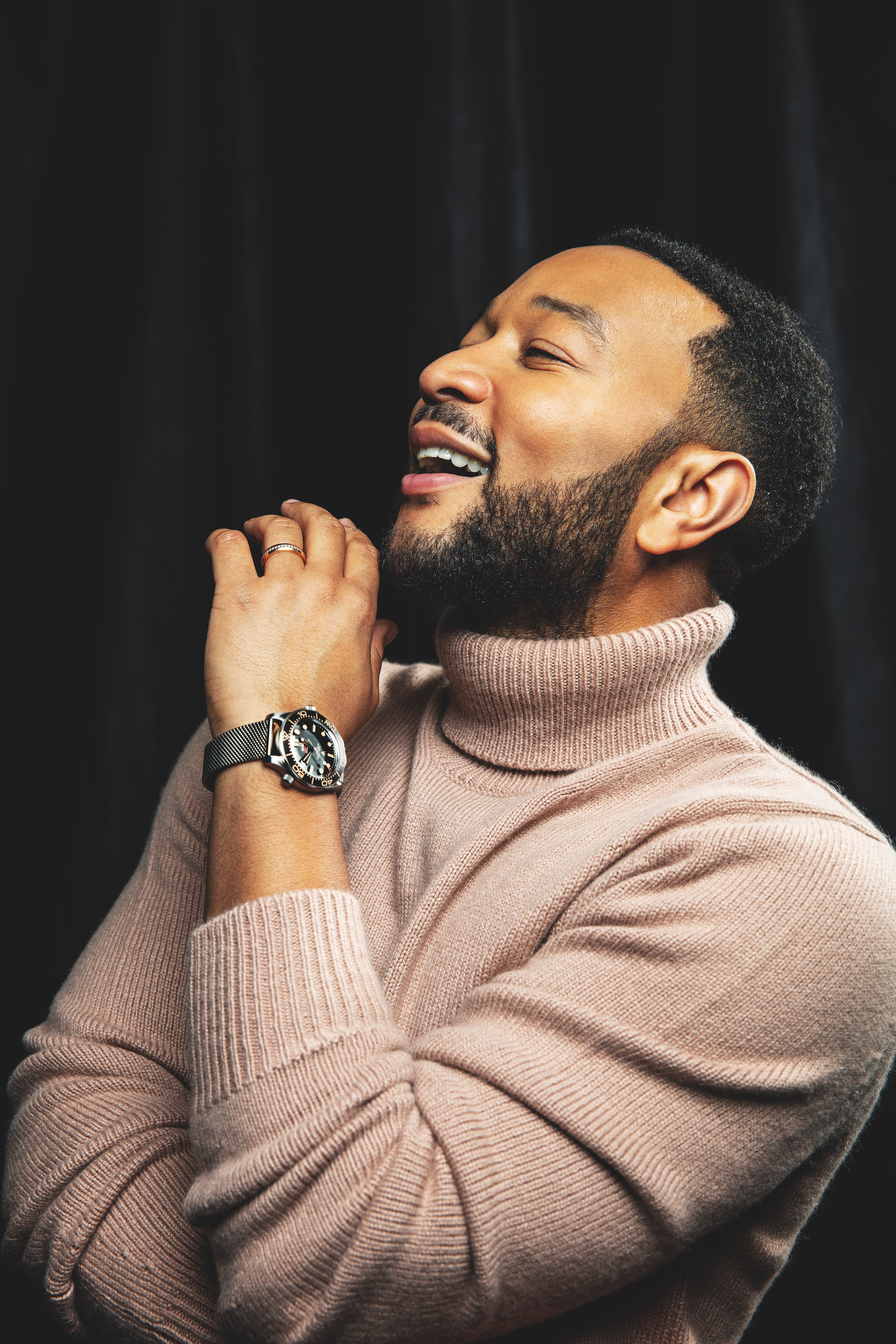 John Legend wearing pink polo neck jumper with omega watch