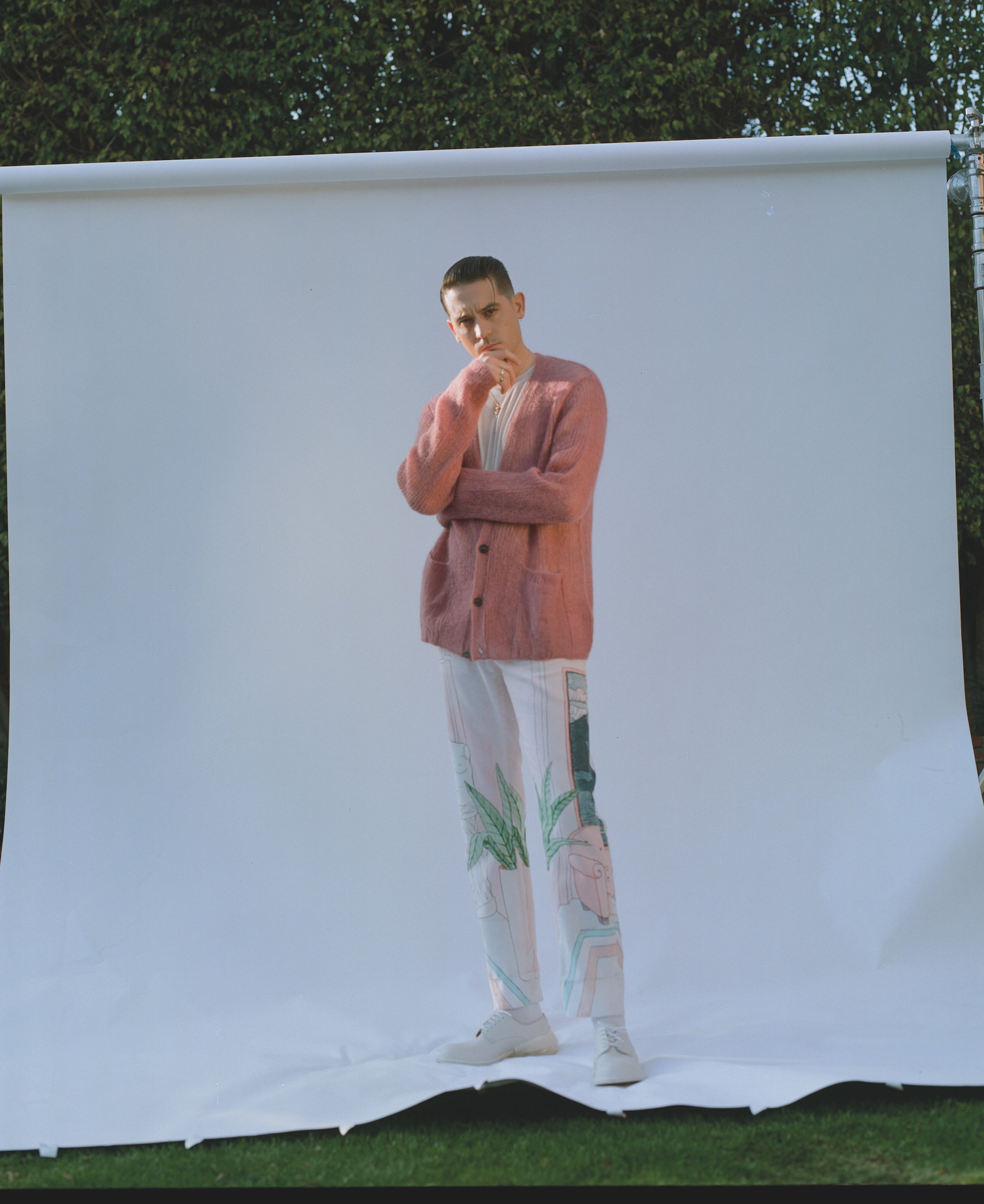 G Eazy wearing a pink cardigan and white trousers
