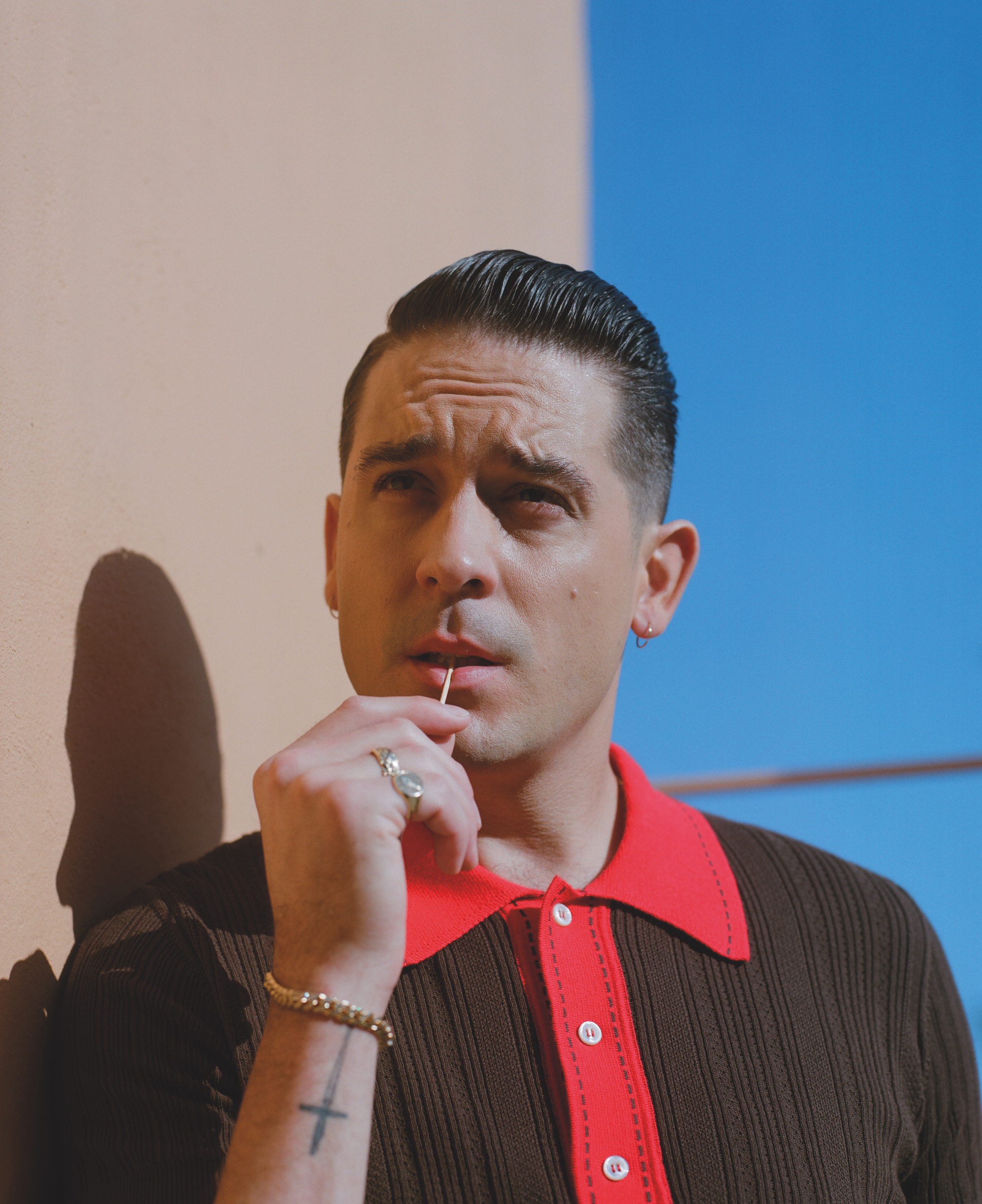 G eazy wearing a red and brown polo neck t-shirt