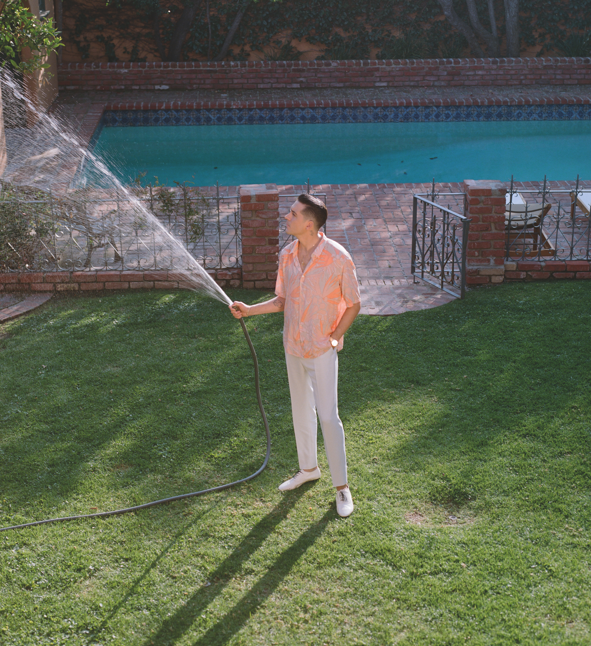 g Eazy in a pink shirt with a water hose.