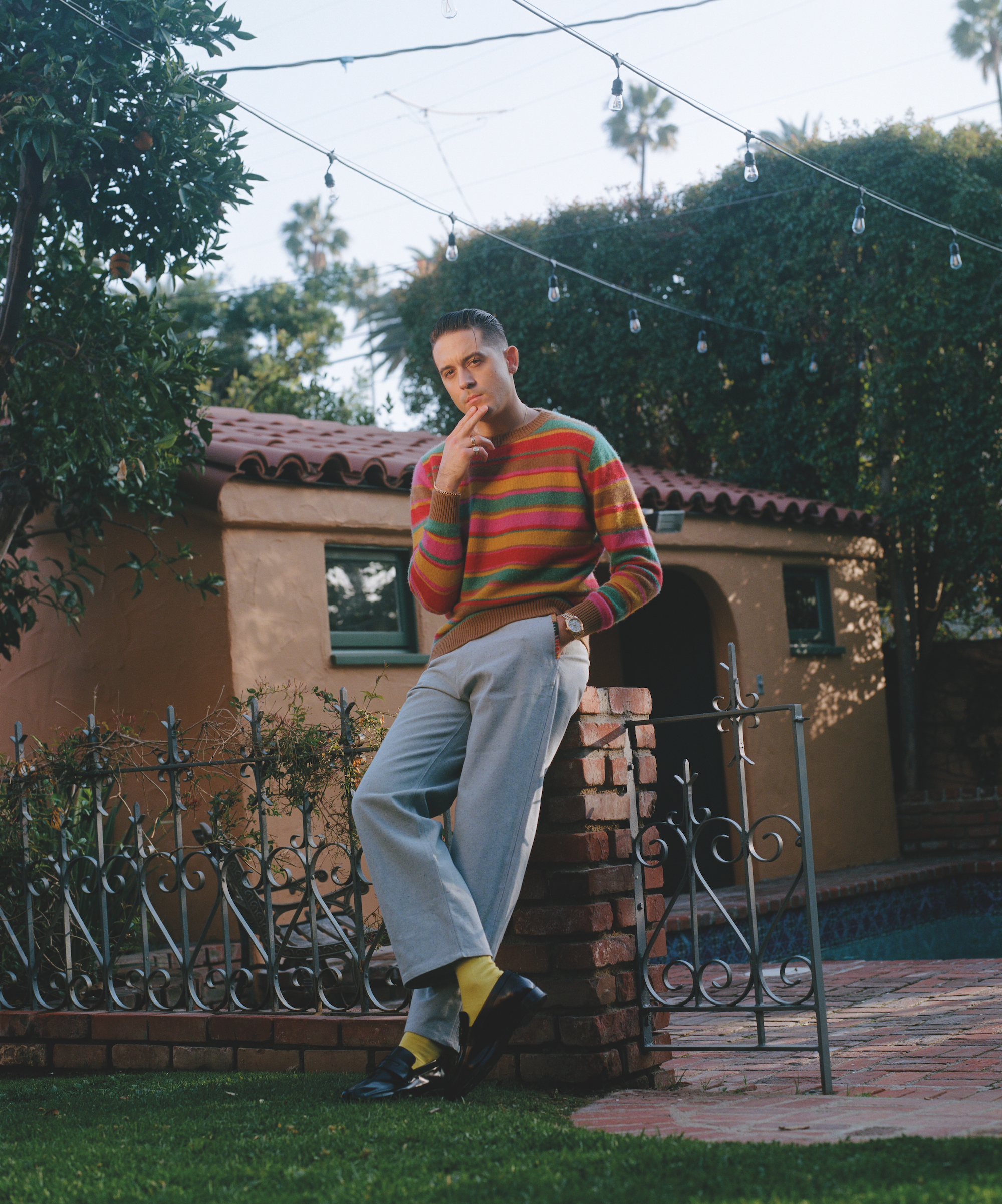 g eazy in a multi-coloured jumper and jeans