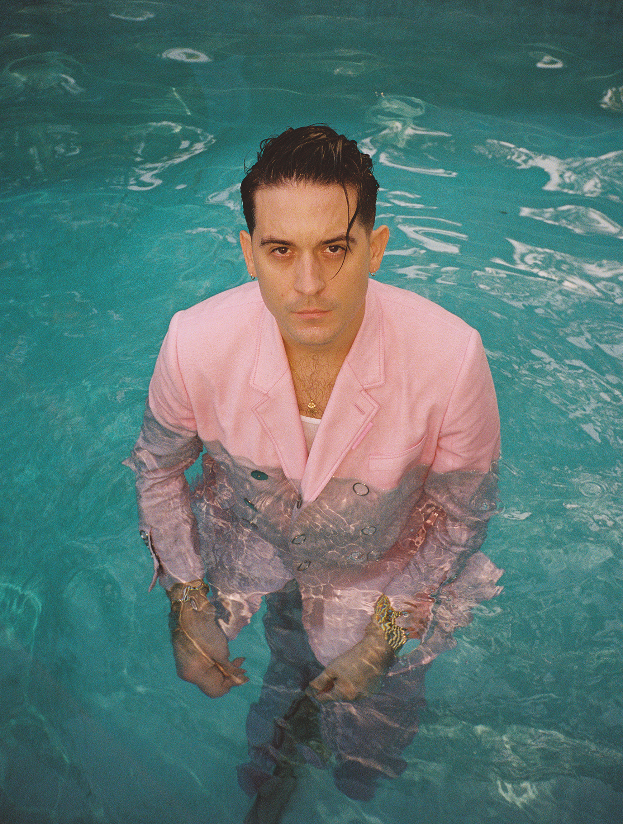 G Eazy wearing a pink suit in a pool