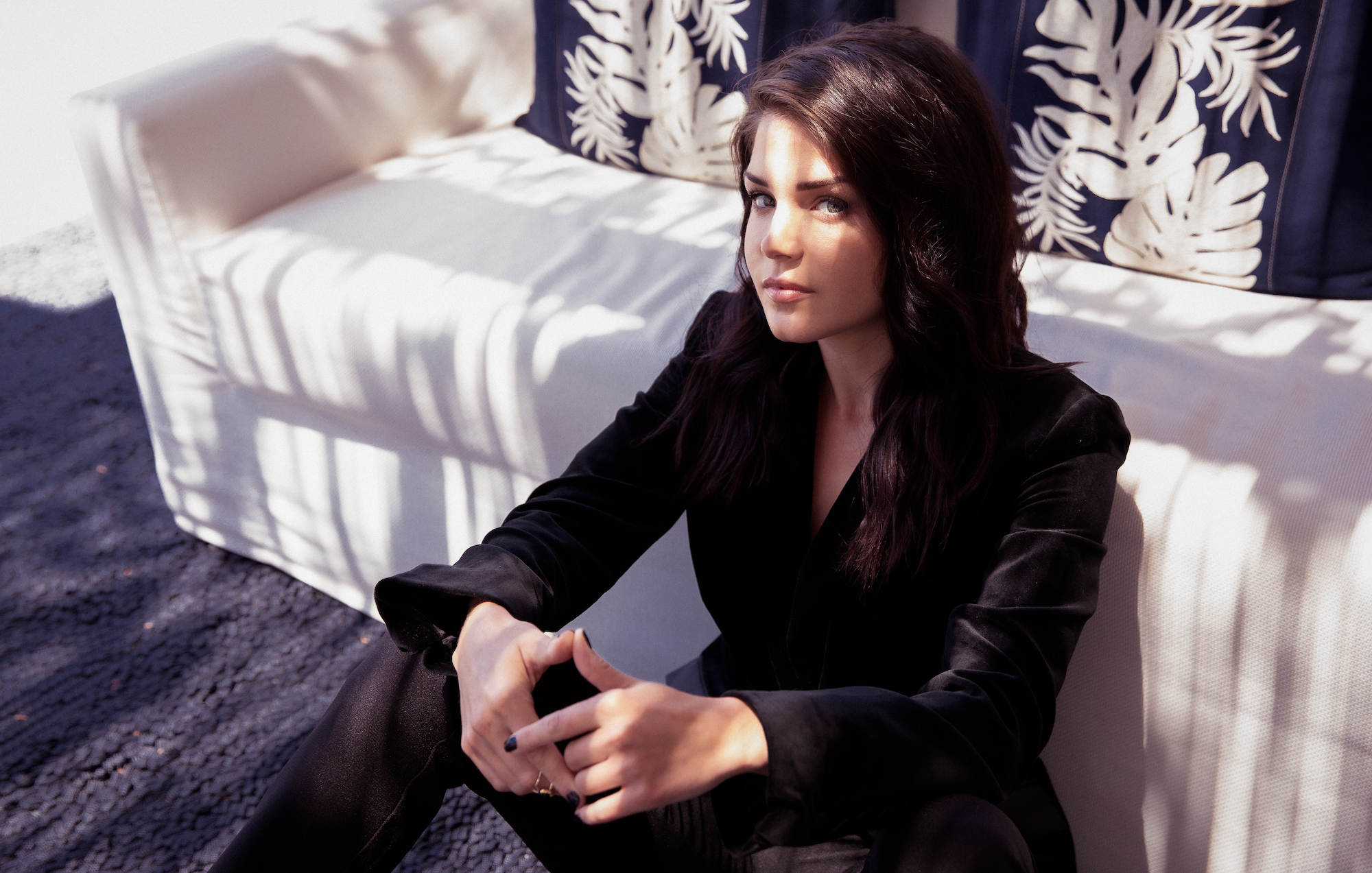 Marie Avgeropoulos wearign all black against white sofa