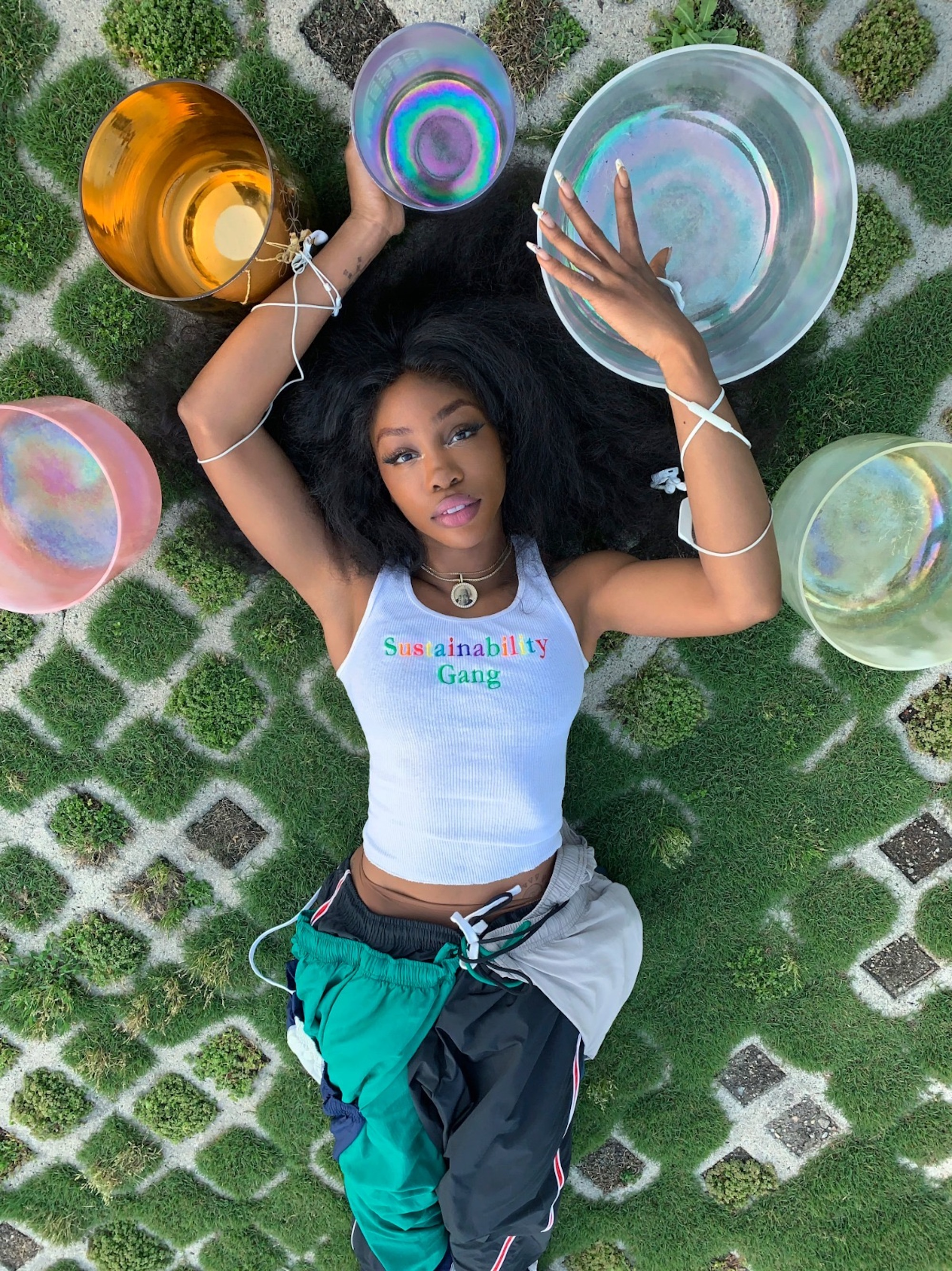 SZA with various bowls of water around her lying the grass