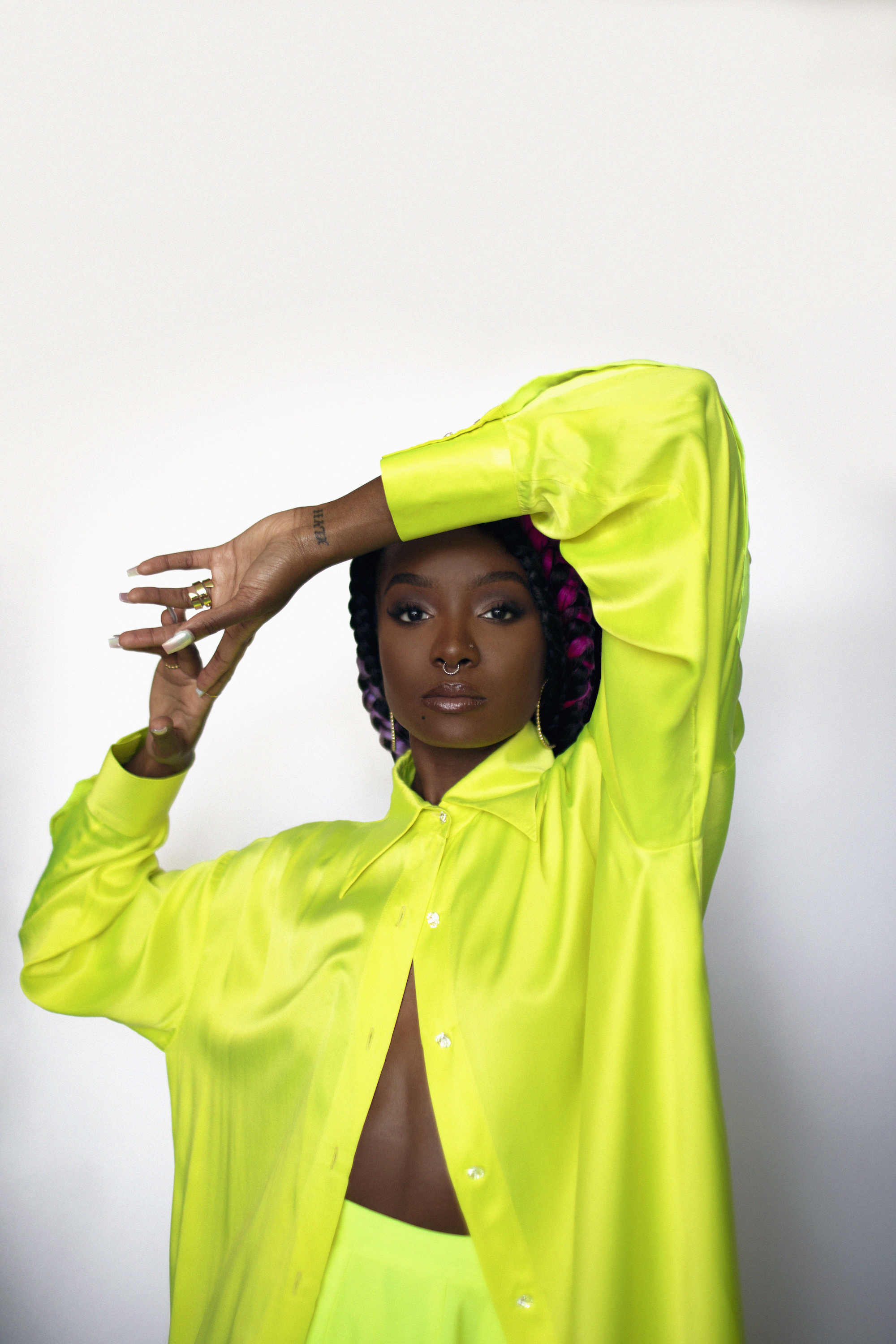 Kiki Layne in bright yellow shirt