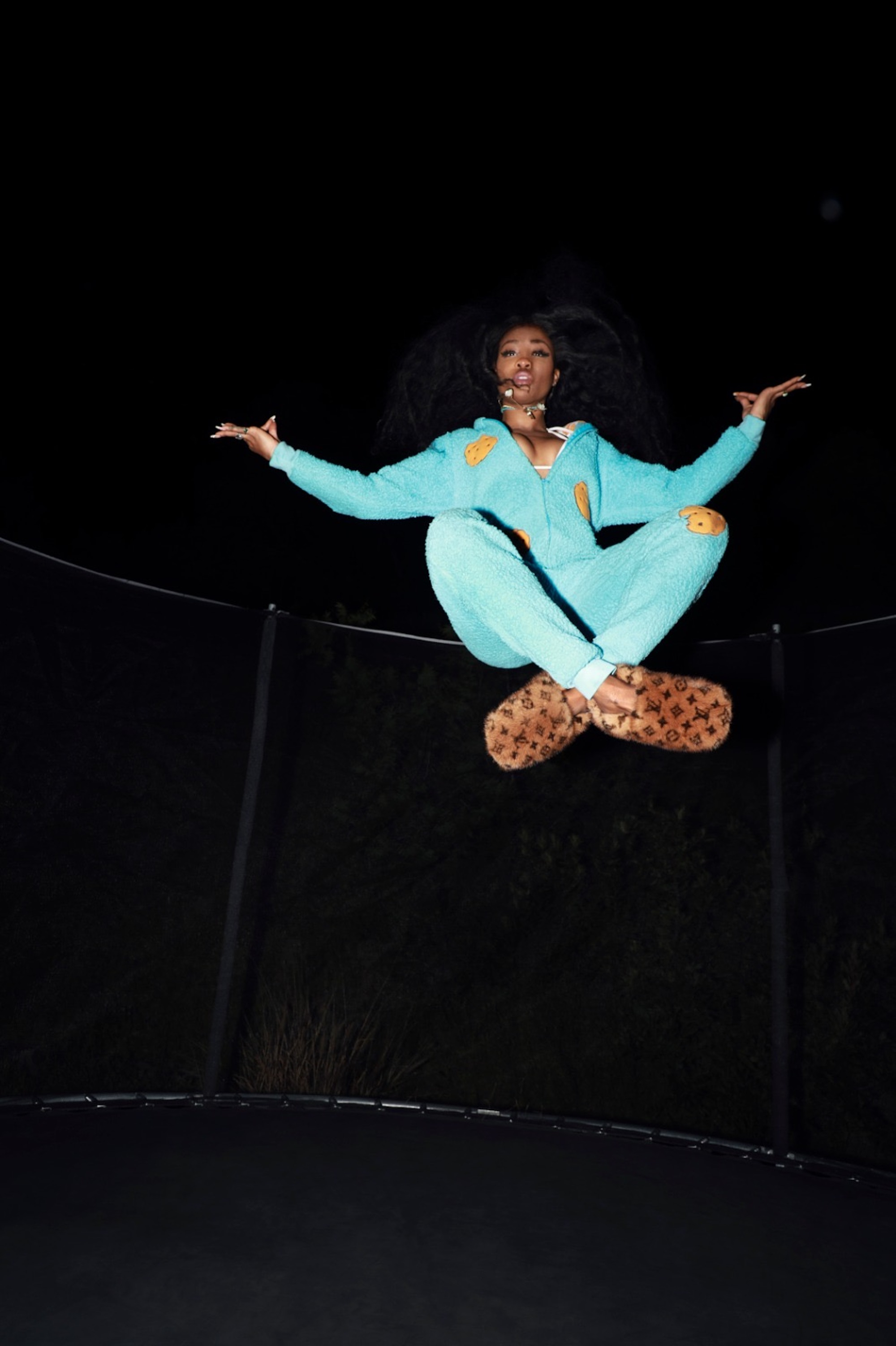 SZA in a onesie jumping on a trampoline