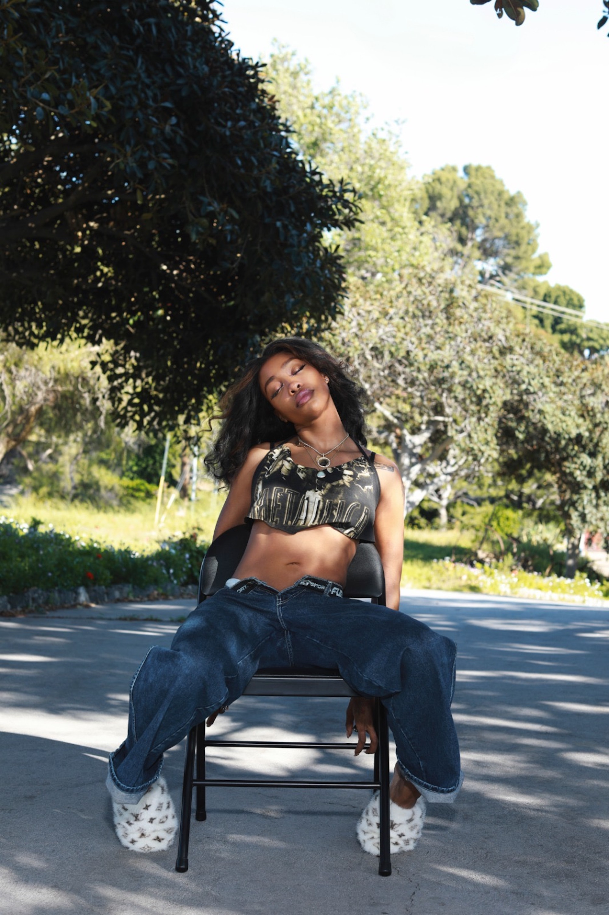 SZA sitting on a chair outside in jeans and green top