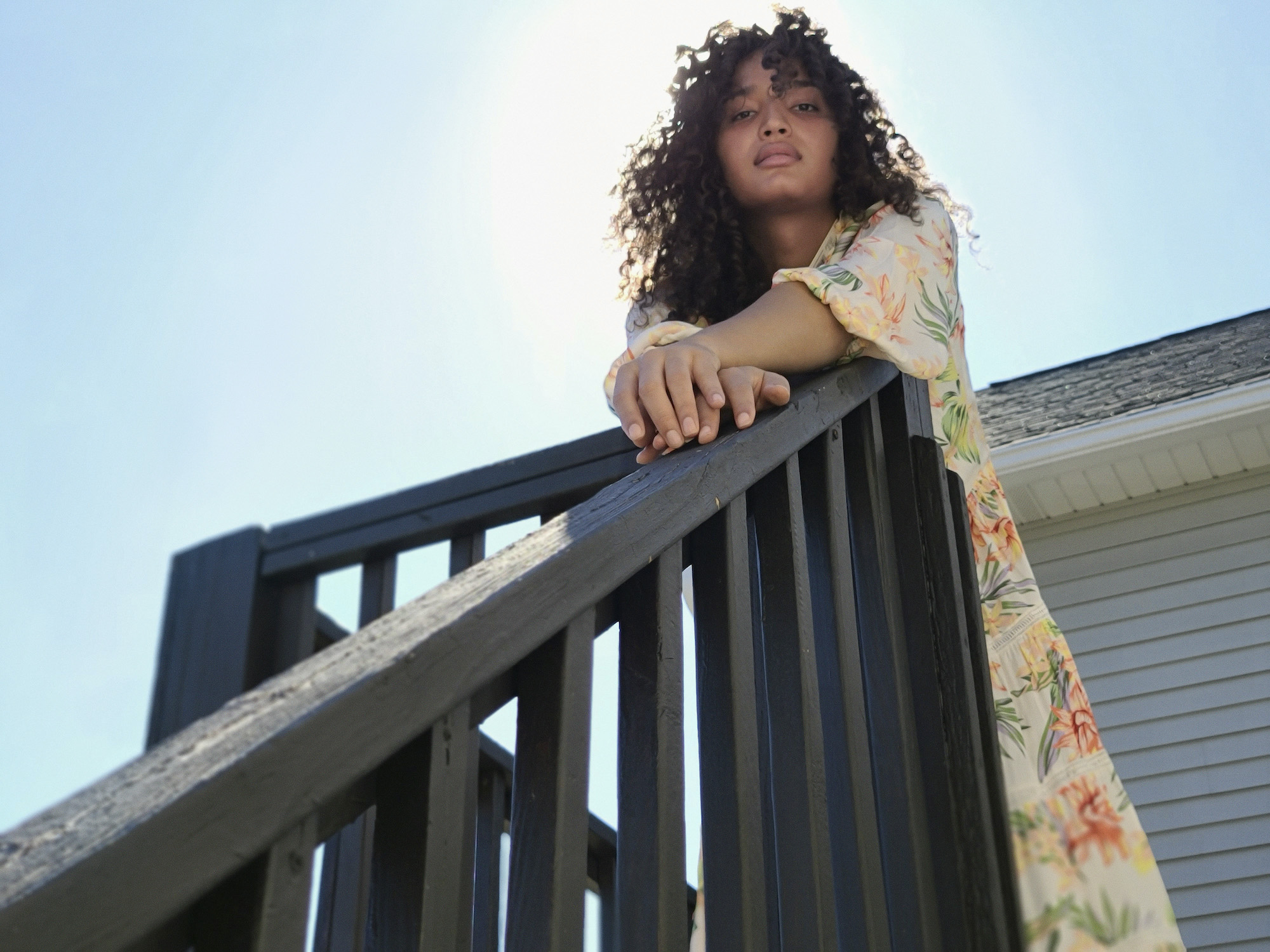 Indya Moore in sundress on stairs