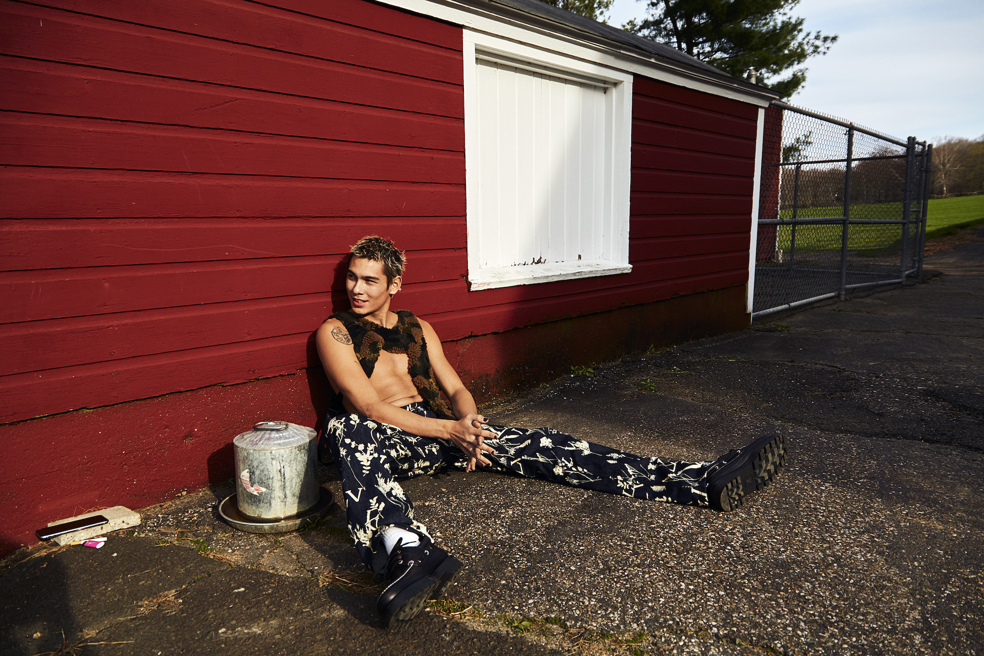 Evan Mock sitting down in printed trousers