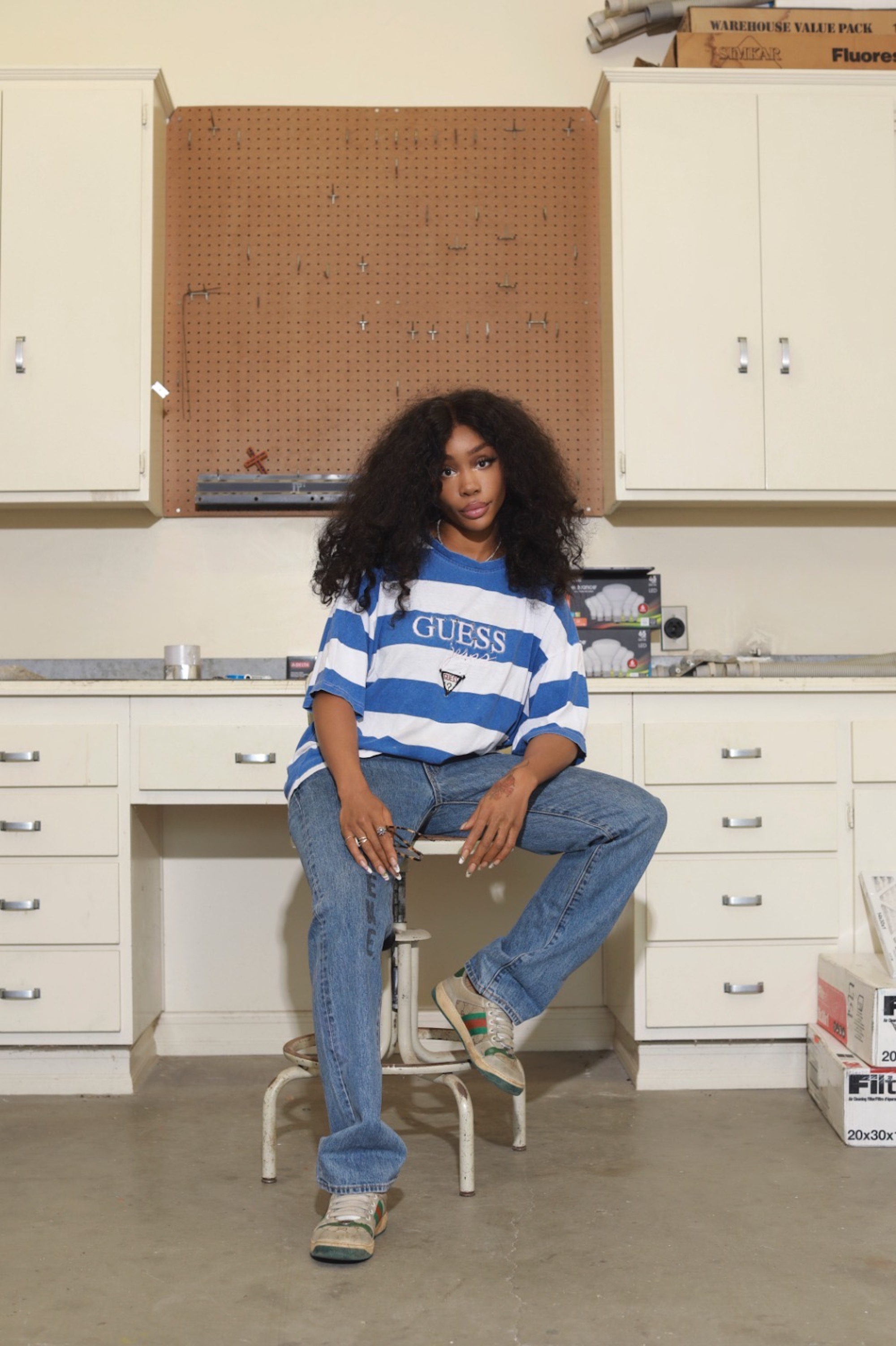 SZA sitting on a work bench in stripe top