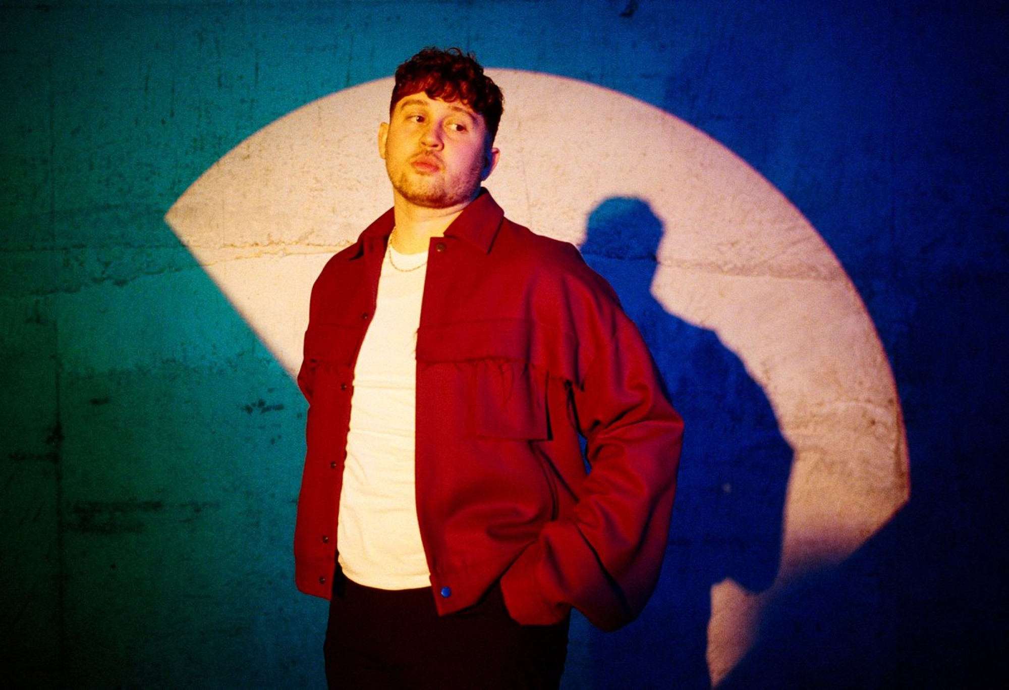 James Vickery, R&B Singer-Songwriter, New Single, Somewhere Out There, wears red shirt in spotlight