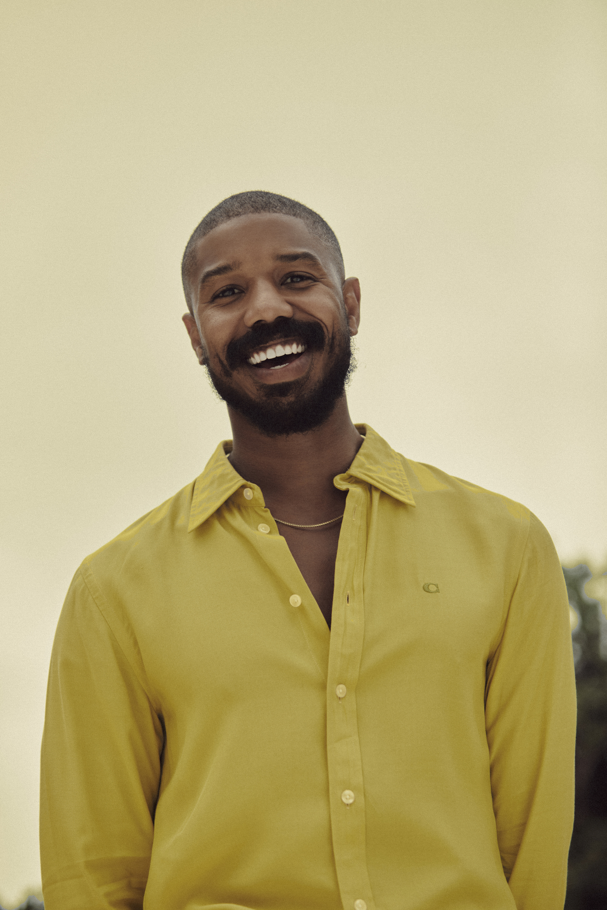 Michael B Jordan wearing yellow COACH shirt for the Autumn 2020 issue of Wonderland
