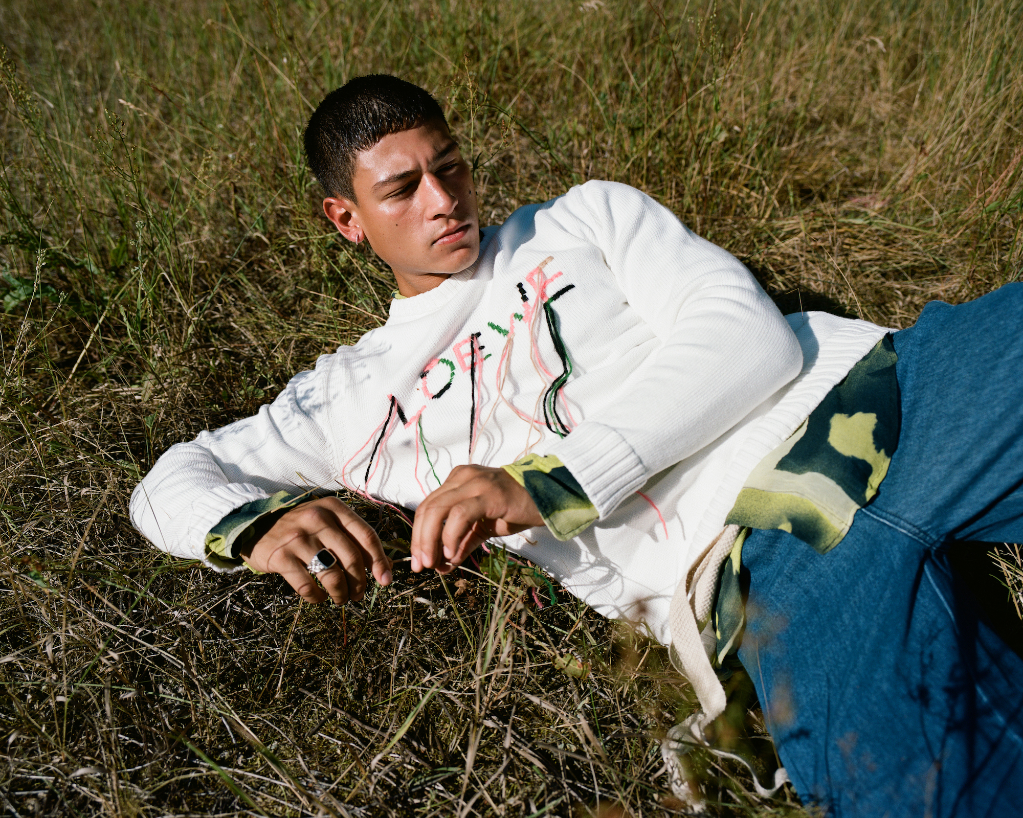 Emilio Sakraya in white jumper and blue jeans lying down
