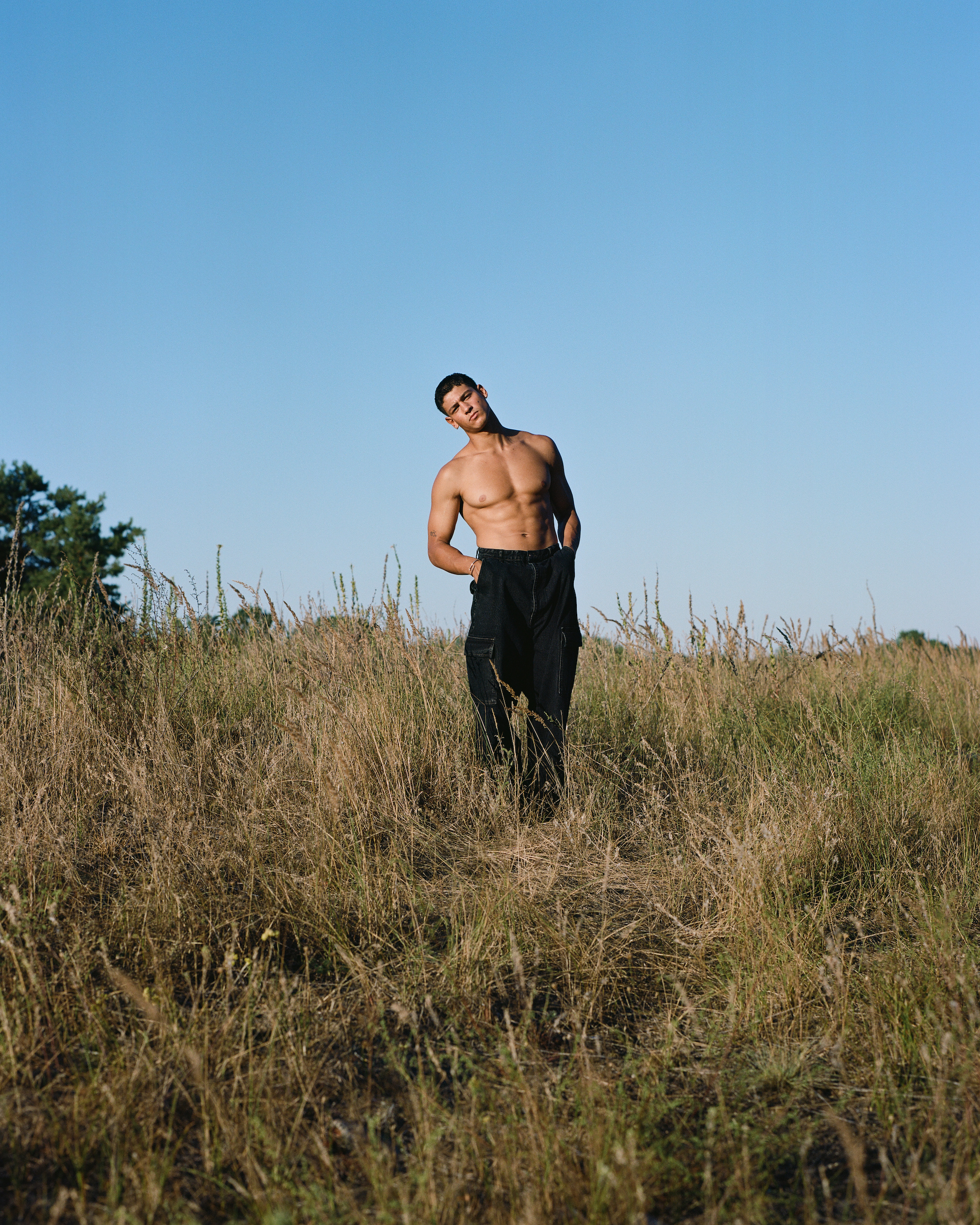 Emilio Sakraya shirtless in black trousers standing in field