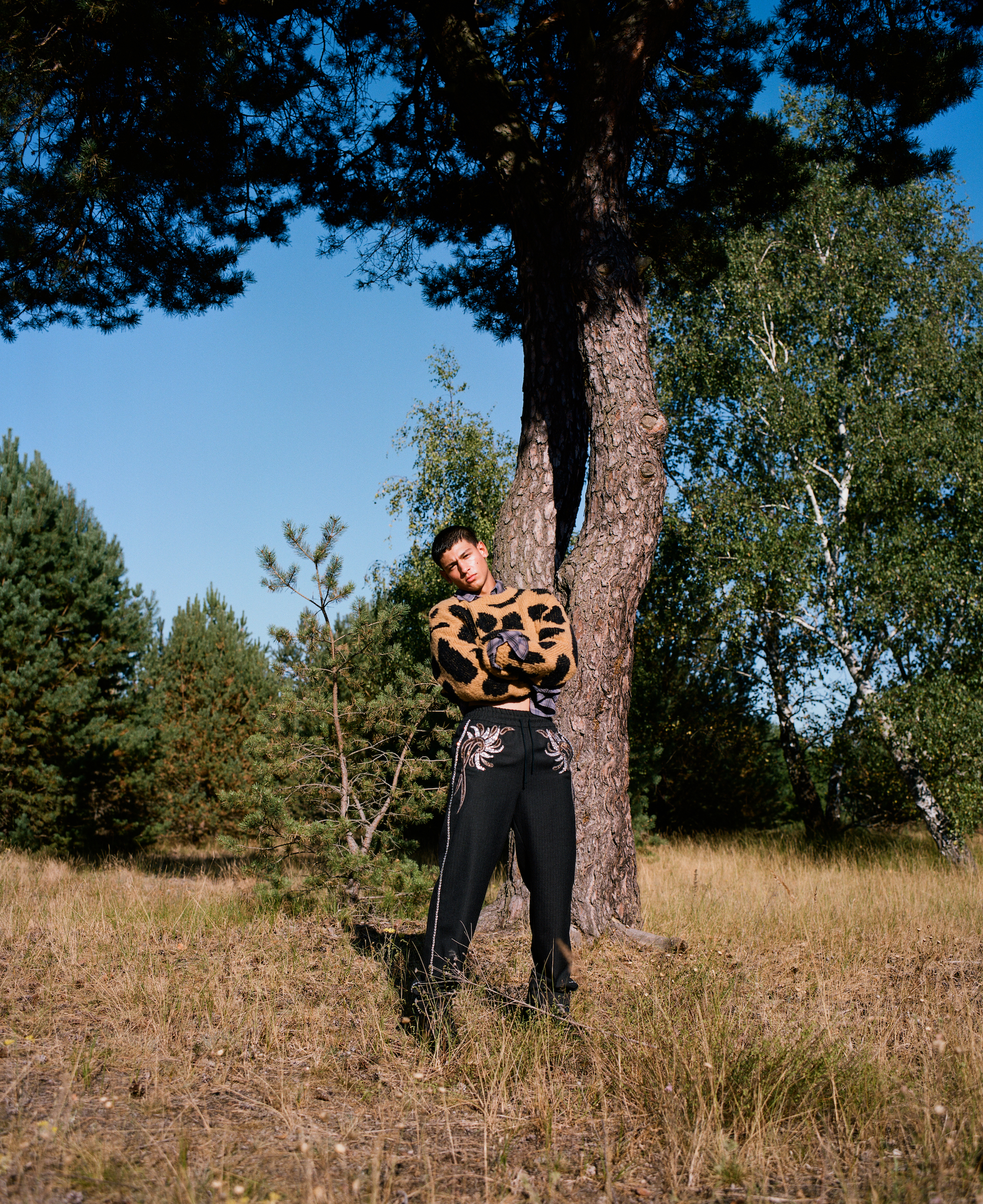 Emilio Sakraya shirtless in jumper and black trousers standing by tree