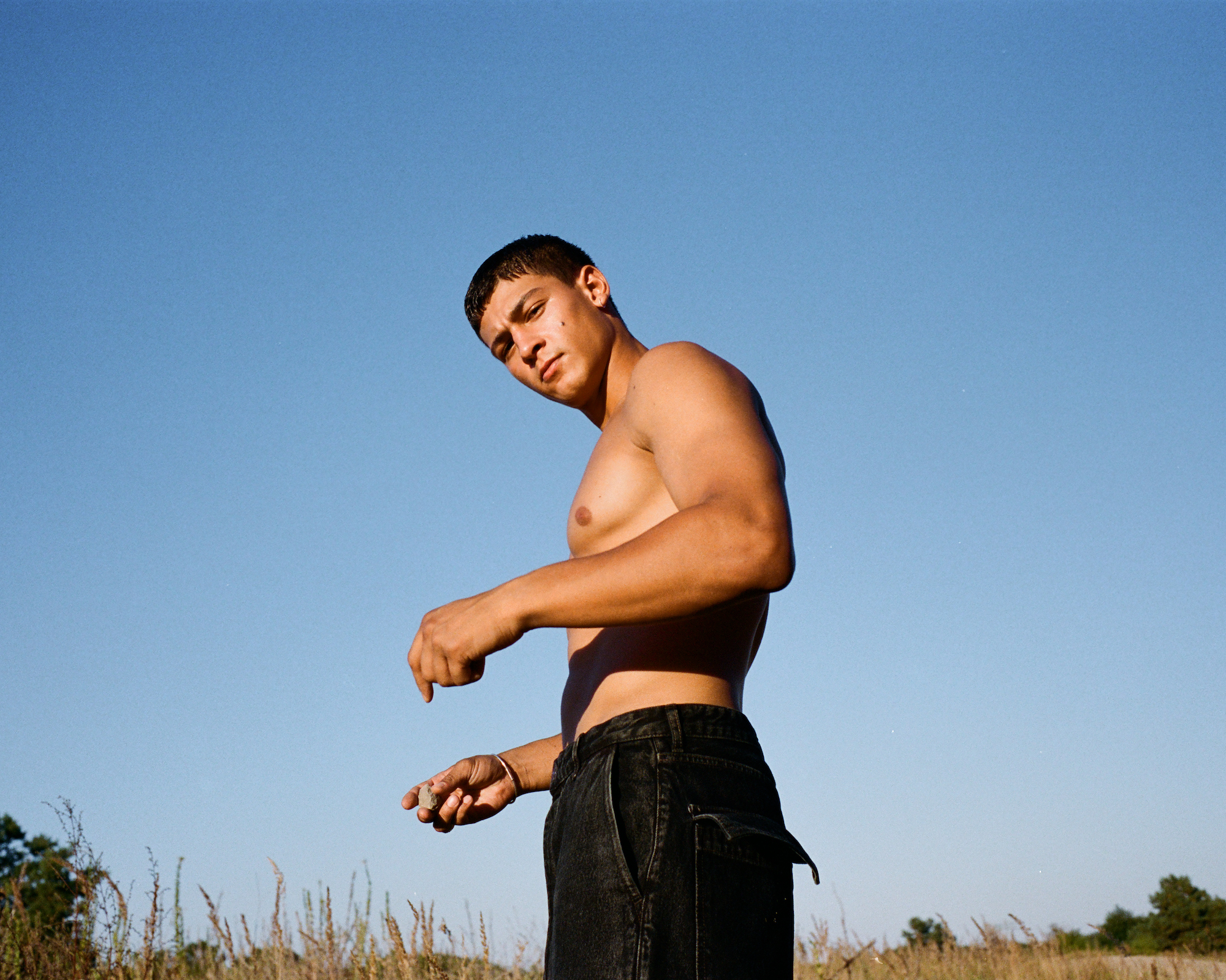 Emilio Sakraya wearings shirtless standing in field