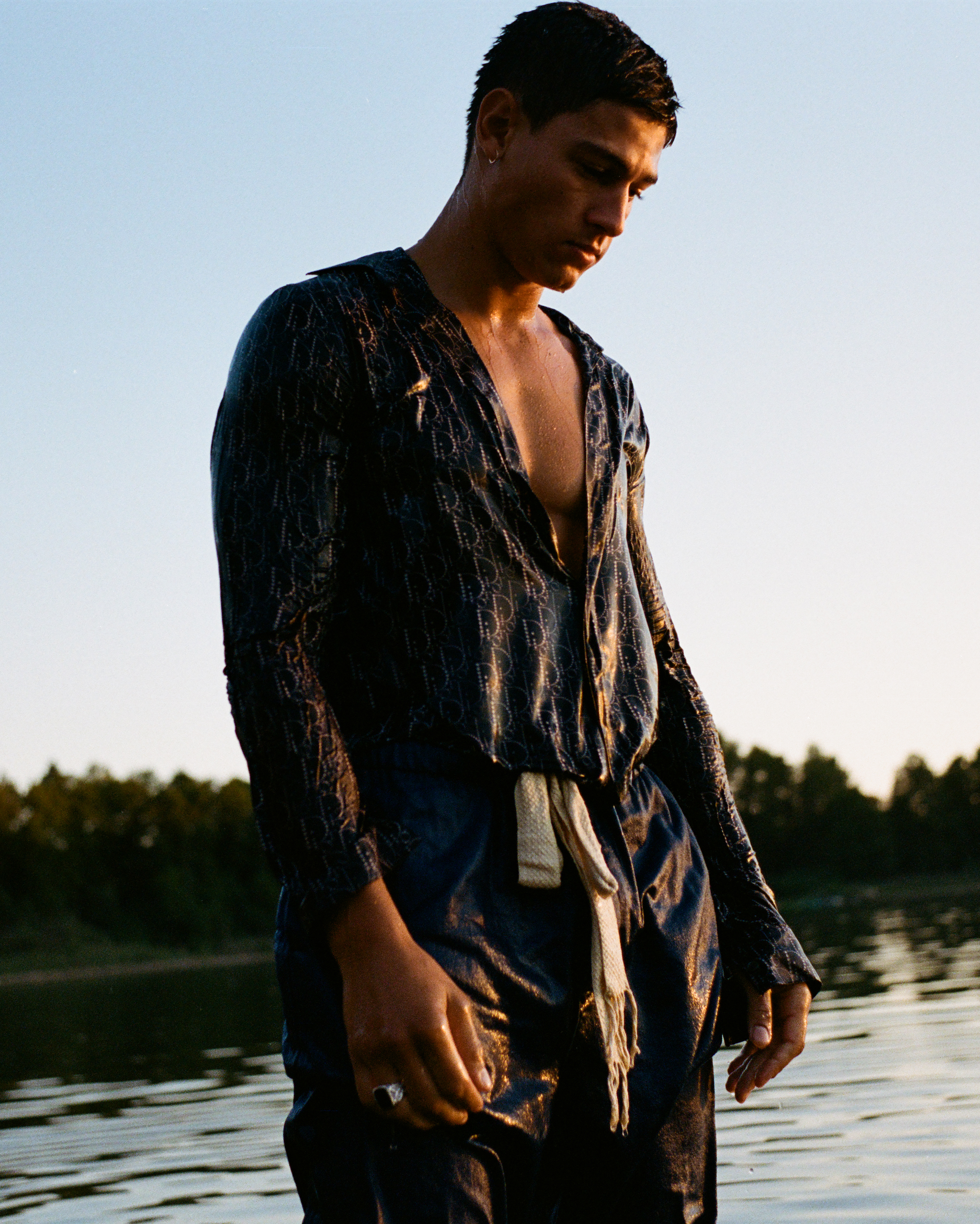 Emilio Sakraya wearings in loose fitting clothing in a river