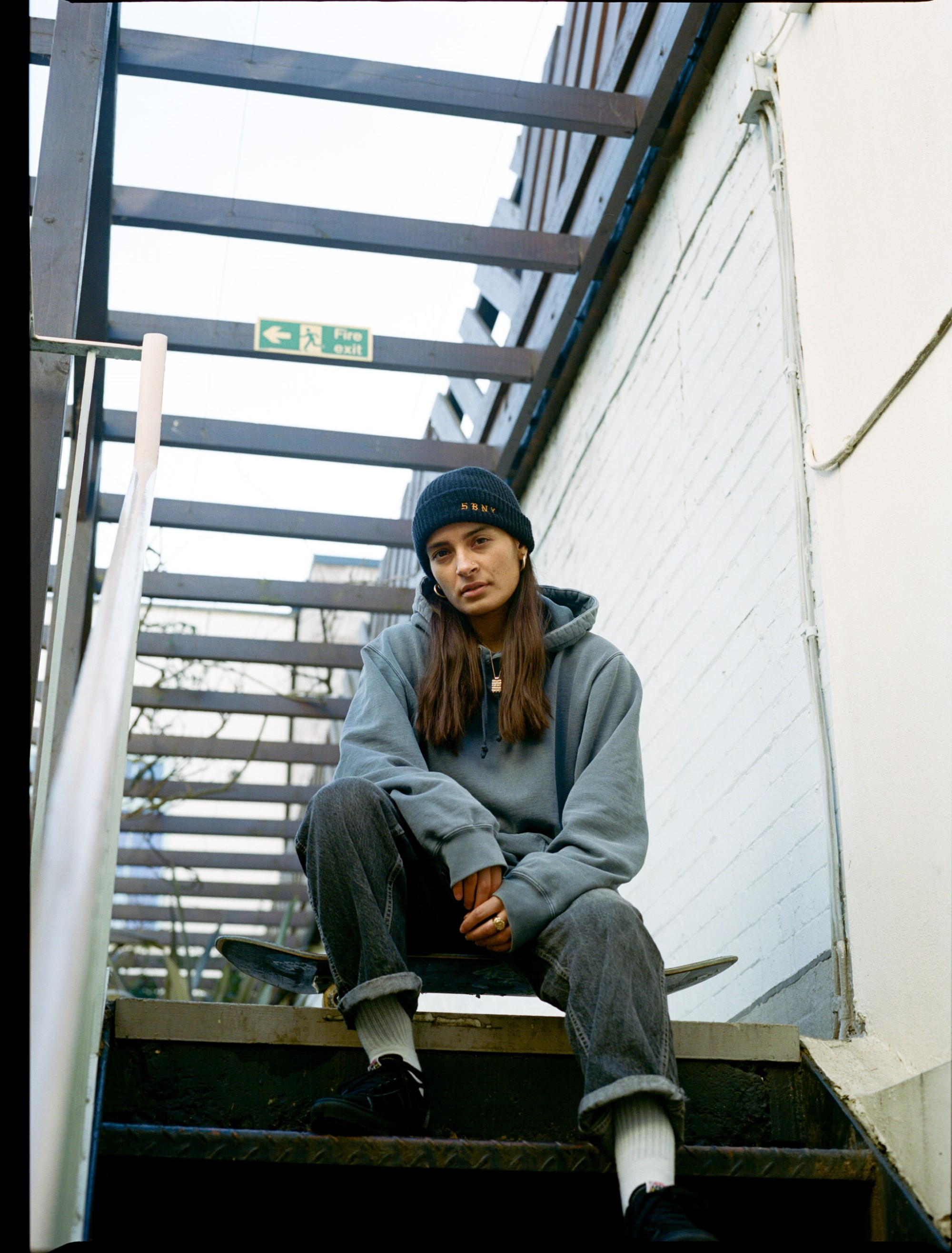 Kavita Babbar, female skateboarder, photographer, producer, Indian British, photograph by Sam Elstub, she sits on skateboard at the top of steps