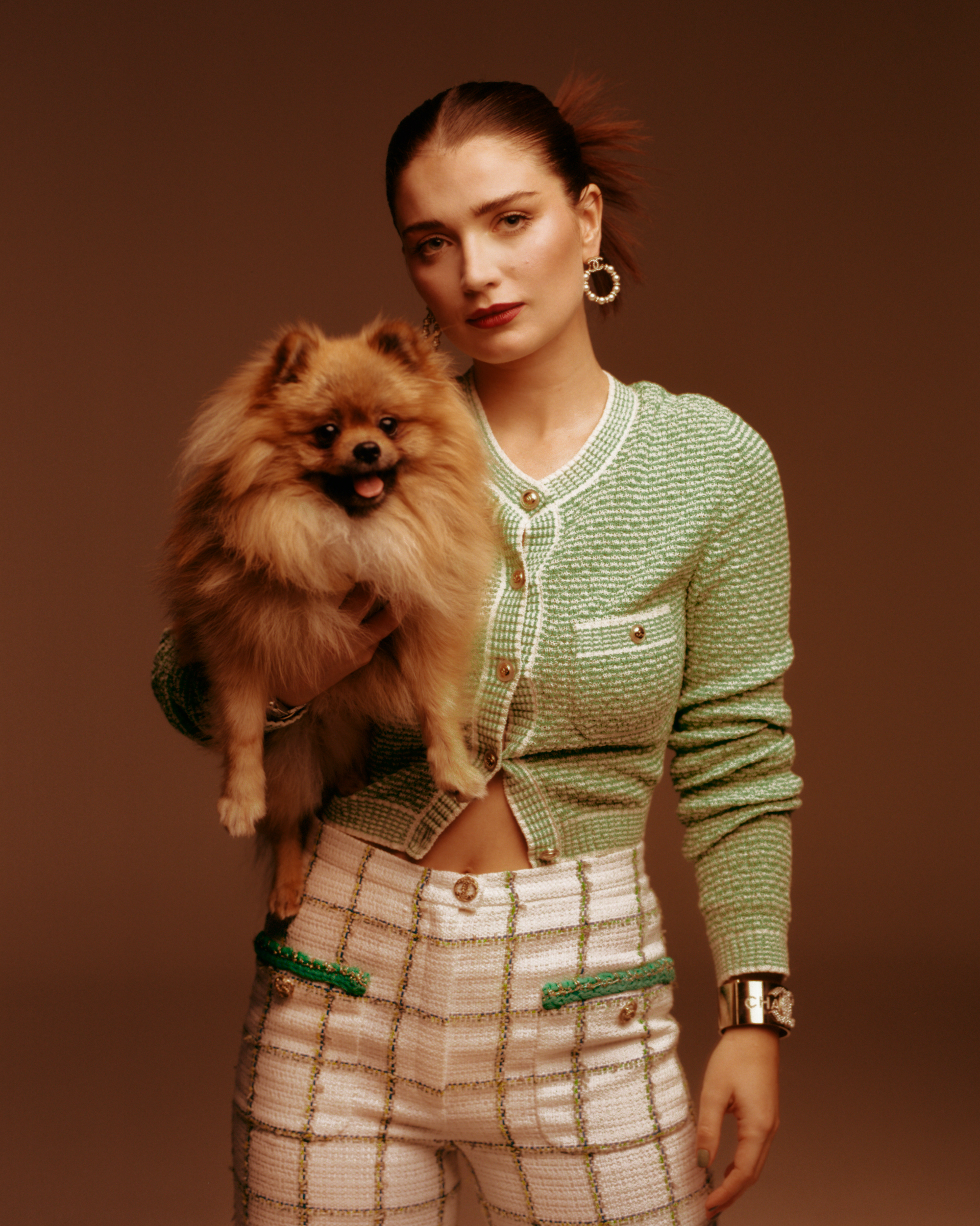 Eve hewson standing with dog wearing green cardigan and skirt