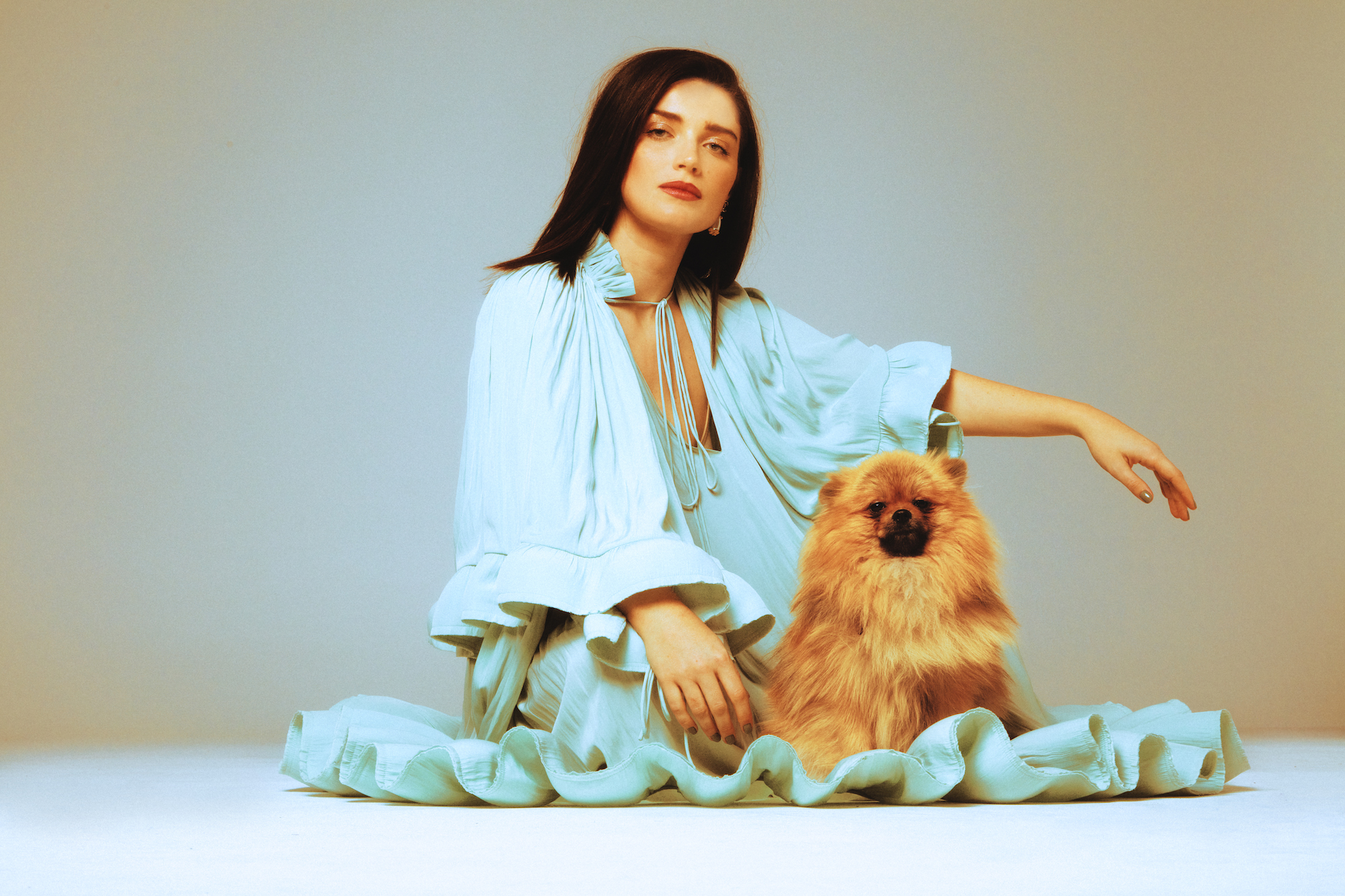 Eve Hewson wearing blue dress with dog